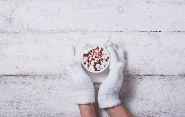 마쉬 멜 로우 컵을 들고 장갑 낀된 손 무료 사진