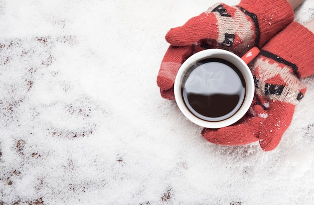 Gloved hands holding hot coffee mug  on white snow