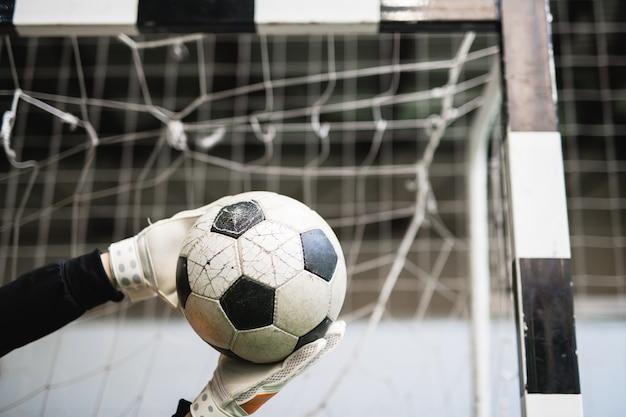 Руки успешного вратаря в перчатках поймали футбольный мяч против сетки в воротах во время игры в футбол