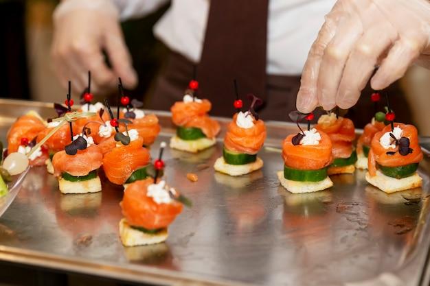 ウェイターの手袋をはめた手が魚とカナッペをレイアウトします。ビジネスミーティング、イベント、お祝いのケータリング。