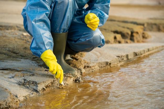 Руки молодой женщины-эколога в перчатках, сидящей у потока грязной воды в загрязненном районе и берущей образец токсичной почвы для изучения ее характеристик