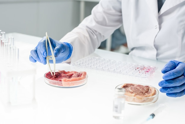 Gloved hands of scientific researcher in whitecoat taking tiny sample of raw vegetable meat during experiment while sitting by table in laboratory