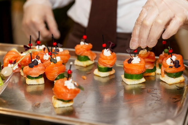Gloved hands of the waiter lay out canapes with fish. catering for business meetings, events and celebrations.