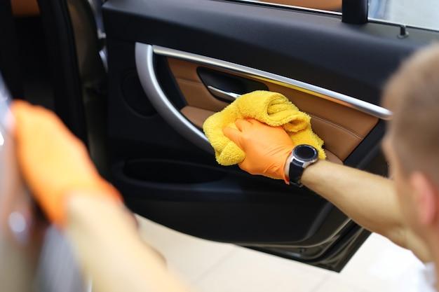 Разнорабочий в перчатках протирает двери машины внутри кабины крупным планом