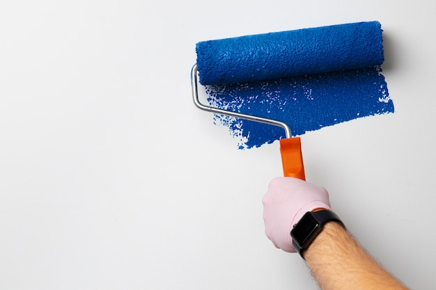Gloved male hand painting wall into classic blue color