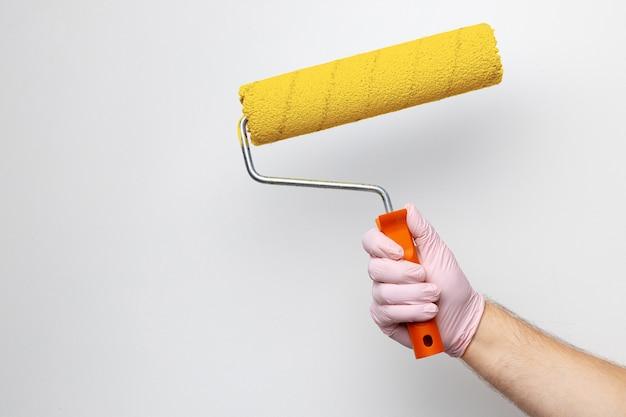 手袋をはめた男性の手塗りの壁を明るい黄色に