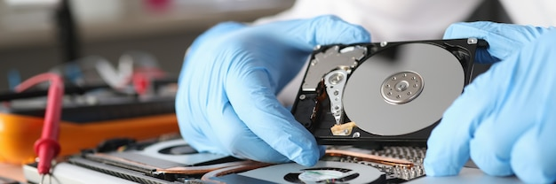 Gloved master holds a hard drive diagnostics and repair of computer equipment concept