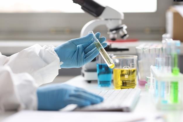 장갑을 낀 과학자는 키보드 화학 물질에 투명한 액체와 유형이 있는 테스트 튜브를 들고 있습니다.