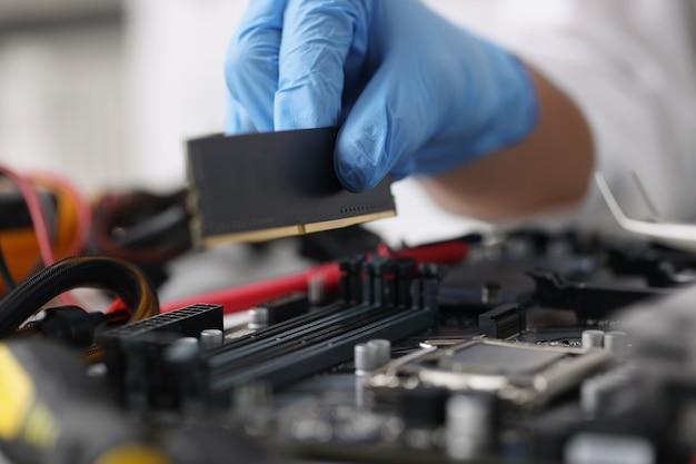 장갑을 낀 기술자가 고장난 컴퓨터 장비 수리 서비스 개념을 진단합니다.