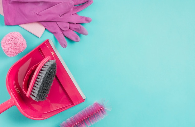 Gloves, dustpan, scrub and brush on turquoise background