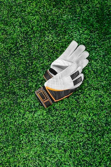 Gloves of the goalkeeper on a green lawn