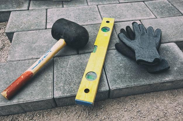 Перчатки, молоток и строительный уровень на брусчатке