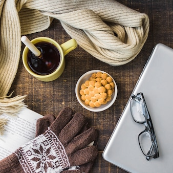 Gloves and scarf near dessert and notebook