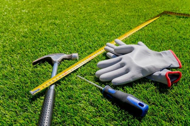 Перчатки, отвертка, молоток и метр на искусственной траве.