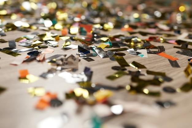 床に輝く金色の紙吹雪は、金の金属製のパーティーの装飾のお祝いの装飾の輝きをクローズアップします