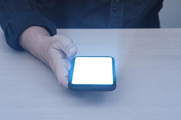 남자의 손에 전화의 발광 조명. 빛나는 조명 효과와 스마트 폰 빈 화면을 들고 손을 닫습니다.