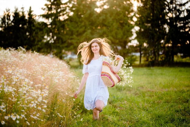 글로우 썬. 필드, 태양 빛에서 실행되는 흰 드레스에 아름 다운 모델 소녀. 무료 행복한 여자. 따뜻한 색상으로 톤. 선택적 초점, 라이프 스타일 가을.