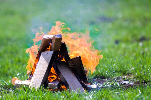 Glowing bonfire on nature. burning wooden planks outside on summer day. bright orange flames, light smoke and dark ashes on green grass on blurred green. tourism and camping concept.