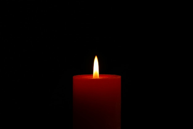 Glowing candle on black, space for text