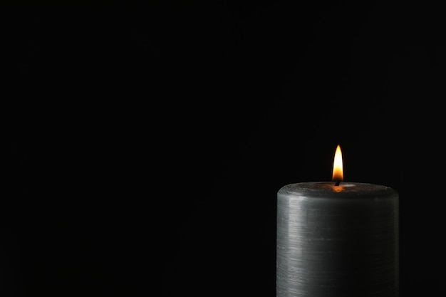 Glowing candle on black