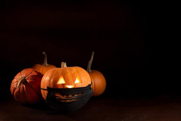 黒の保護薬マスクで輝く刻まれたカボチャ。暗い背景のハロウィーンのカボチャ。