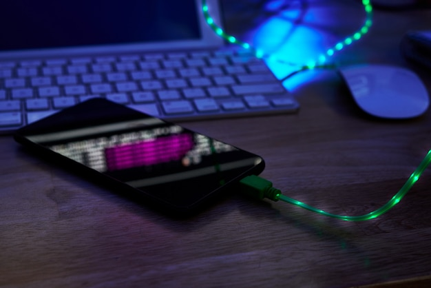 Glowing charging cable in smartphone lying on office table in darkness