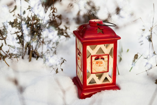 Glowing christmas lantern settled in the snow. outdoor christmas background