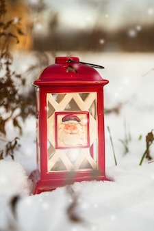 Glowing christmas lantern settled in the snow.
