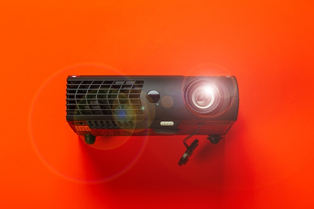 Glowing cinema projector on red background