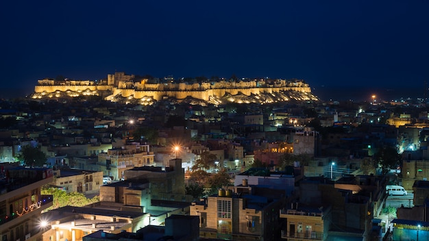 Glowing cityscape at jodhpur at dusk. the majestic fort perched on top dominating the blue town. scenic travel destination and famous tourist attraction in rajasthan, india.