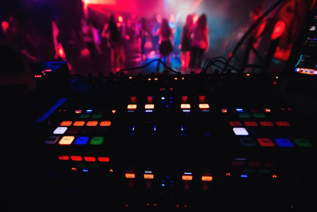 Glowing colorful buttons on mixer dj party night club for dancing
