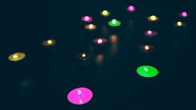 Glowing colorful candles on black background