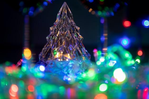 色とりどりの光沢のある花輪の輝くクリスタルツリー新年と黒の背景にクリスマスのお祝い