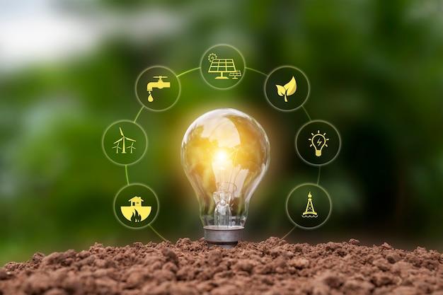 Светящаяся энергосберегающая лампа и значок энергии земли, концепция энергии и окружающей среды.