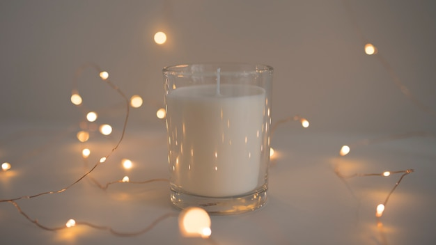 Glowing fairy lights around candle in candleholder