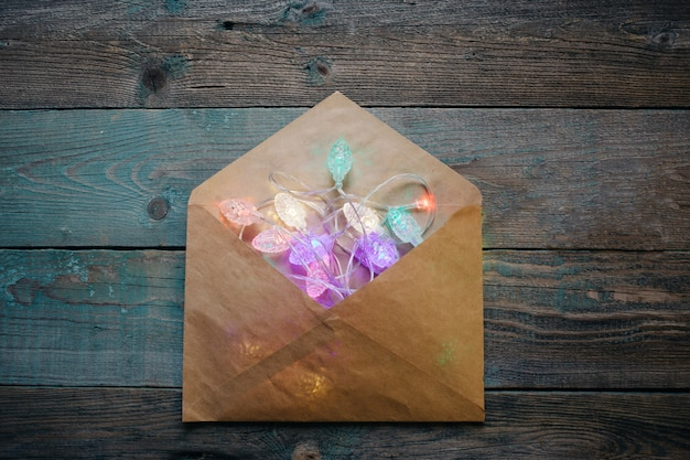 Glowing garland in an envelope, christmas, new year dark wooden flat lay frame