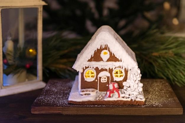 輝くジンジャーブレッドハウス、トウヒの枝の背景。冬の休日の装飾。メリークリスマス、そしてハッピーニューイヤー。