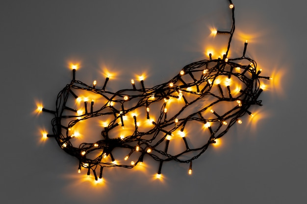 Glowing golden electric garland on a gray background