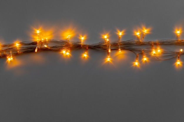 Glowing golden electric garland on a gray surface