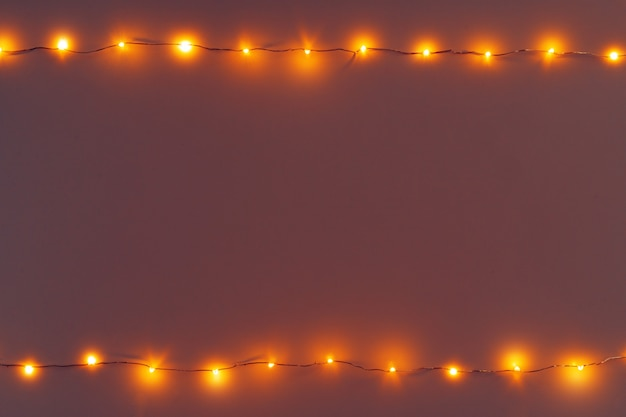 Glowing golden electric garland on a gray wall