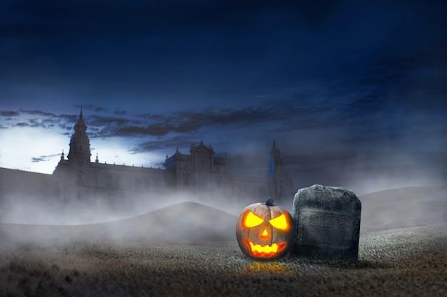 Glowing halloween pumpkin beside grave stones