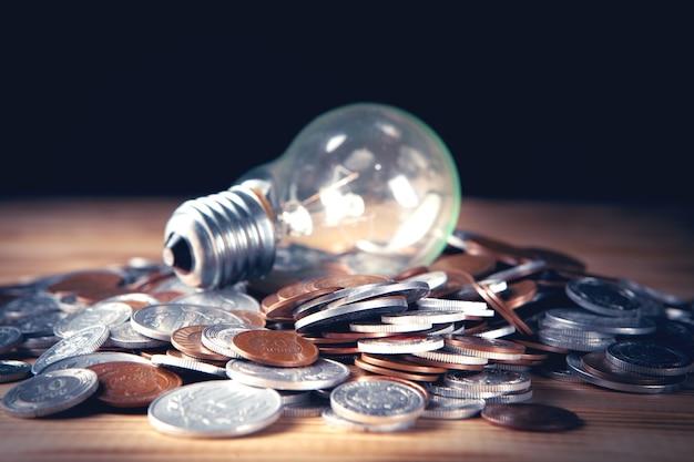 Светящаяся лампа и монеты на темной сцене