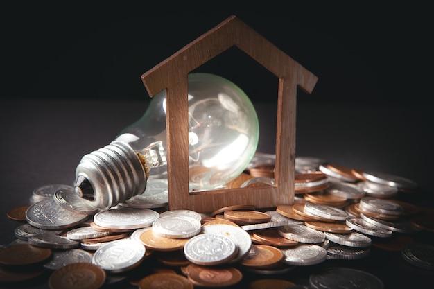 Светящаяся лампа, дом и монеты на темной сцене