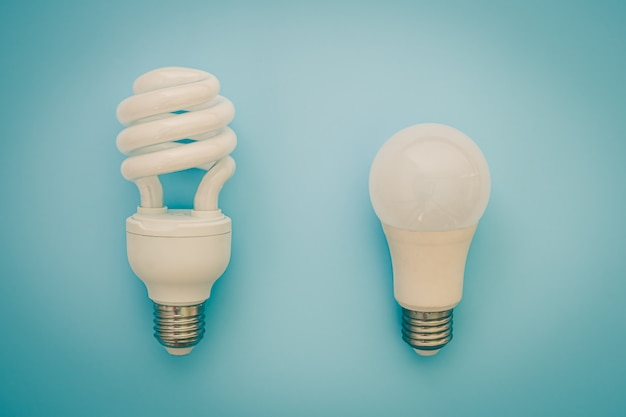Glowing led light bulb on blue background for energy savings concept