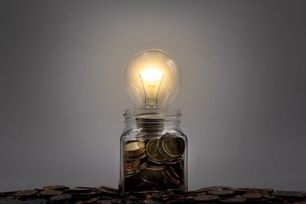 Glowing light bulb on coins in glass jar