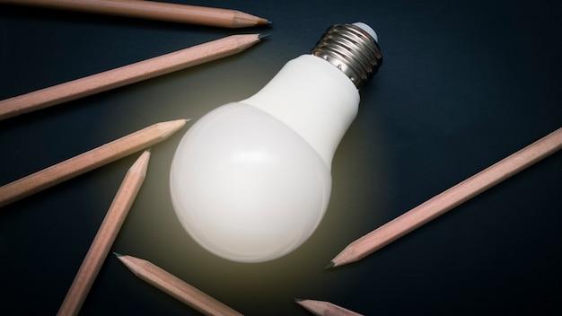 연필, 아이디어와 영감 개념 검은 칠판에 빛나는 전구