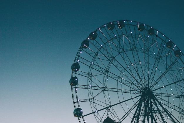 Glowing lights on ferris wheel, resort nightlife, background, beautiful sky. high iso, grain