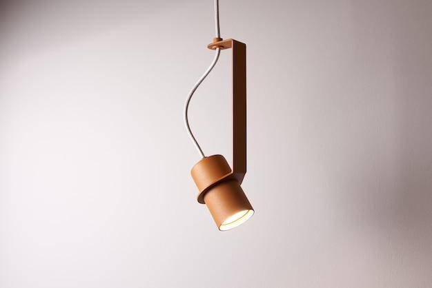 빛나는 금속 주황색 램프가 회색 벽의 케이블에 매달려 있습니다.