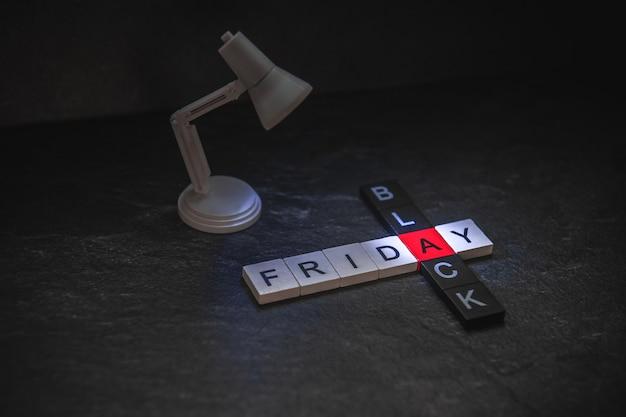 빛나는 현대 램프는 어두운 배경에 비문을 비 춥니 다. 검은 금요일 크로스 워드 퍼즐.