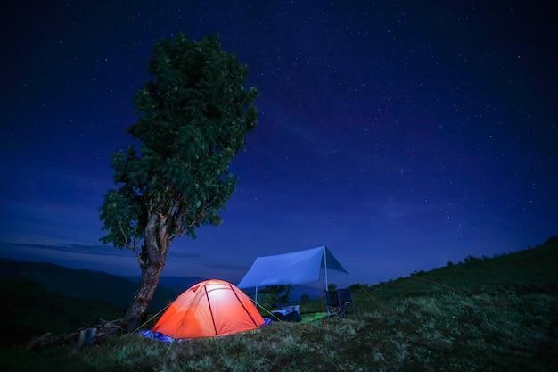 극적인 하늘 아래 산에서 빛나는 주황색 텐트